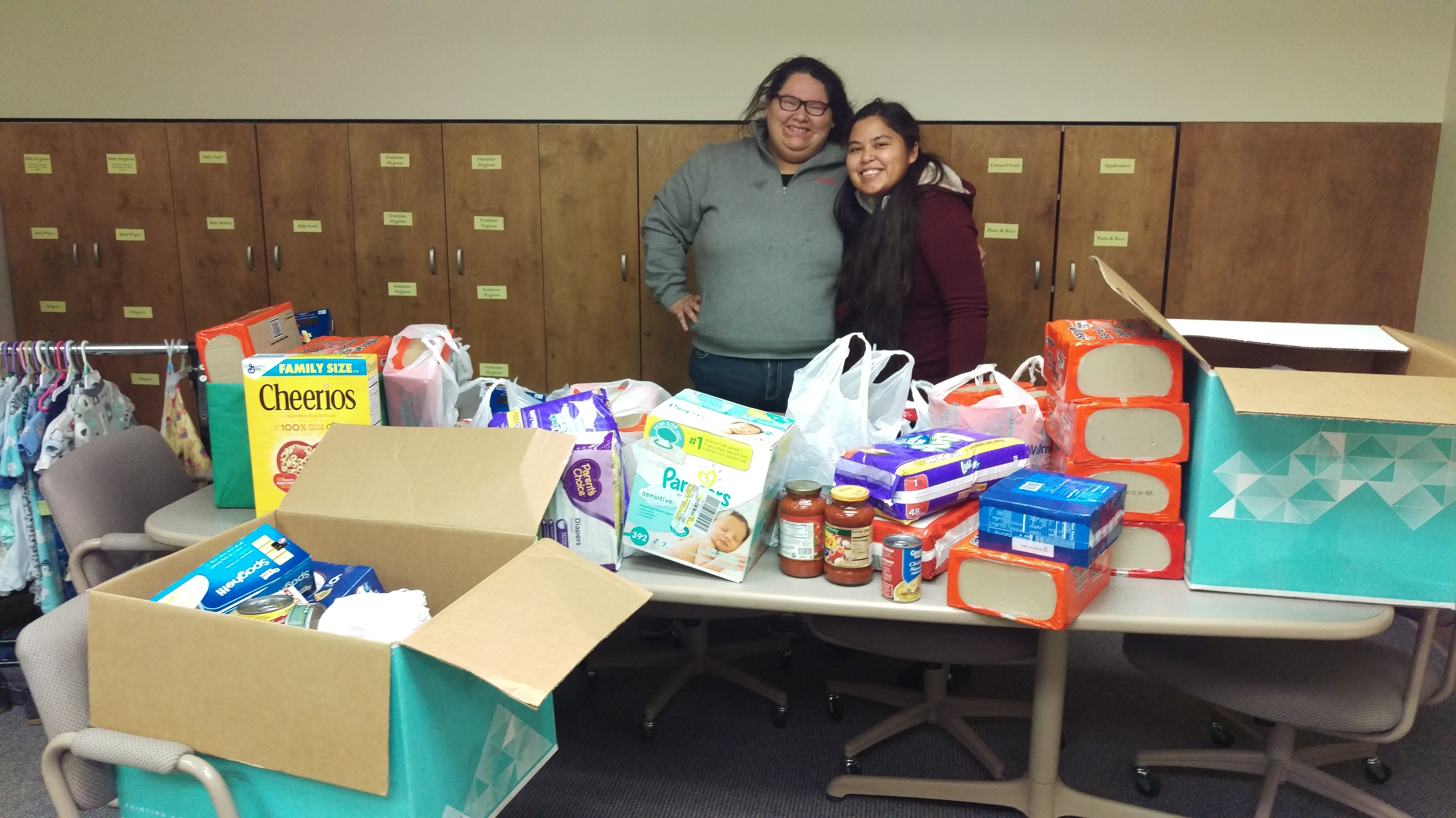 two students standing with a full table of donations