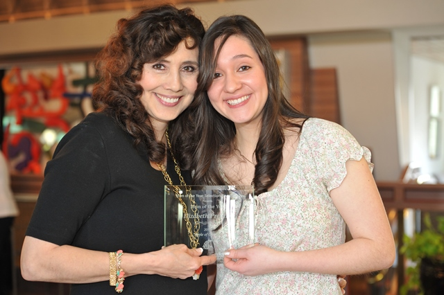 young woman holding an award with her mother