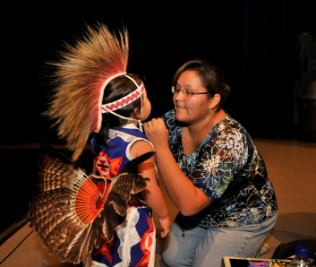 Native woman helping a small child dress in traditional regalia